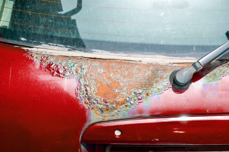 La porte arrière ou cinquième de voiture rouge de berline avec hayon arrière a endommagé les taches rouillées et corrodées de pei photo libre de droits