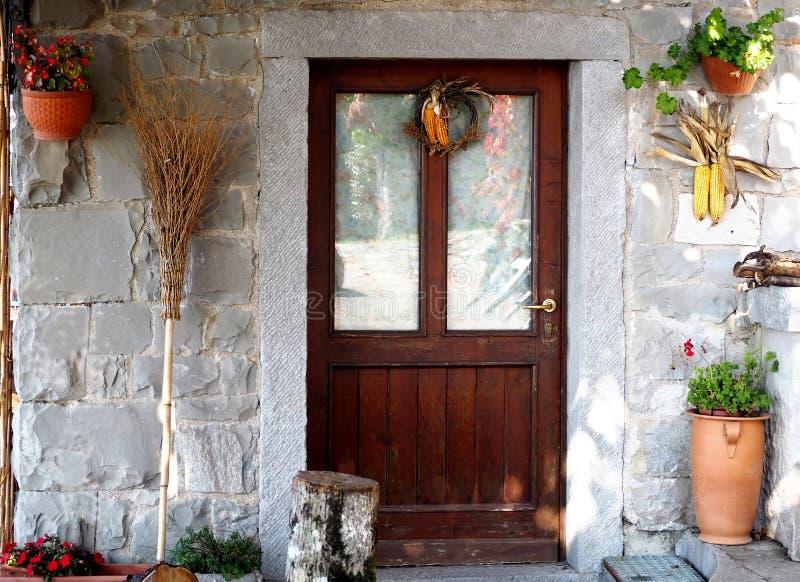 La porte d'entrée d'une maison rurale avec un balai en osier, des épis de maïs et des pots de fleur a accroché sur le mur en pier photos stock