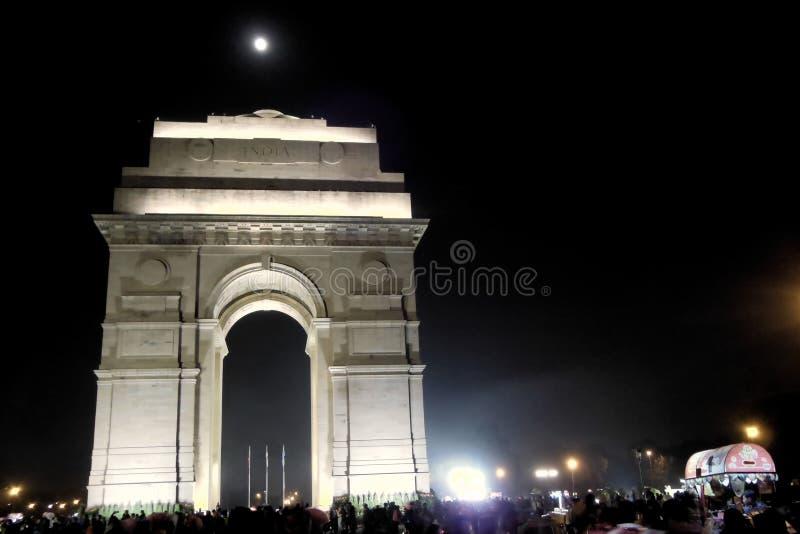 La porte d'Inde décorée dans la lueur de la nuit allume la lune au-dessus des habitants et des touristes non identifiés le 2 déce image libre de droits