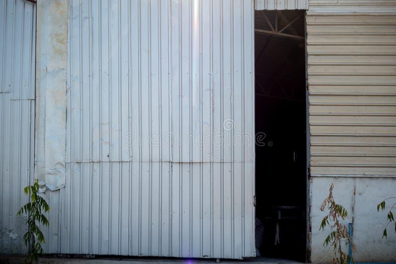 La porte de l'entrepôt qui s'ouvre légèrement pour voir l'intérieur foncé pour le fond photo stock