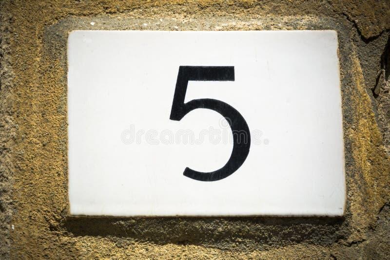La porte le numéro cinq se connectent le mur superficiel par les agents photos stock