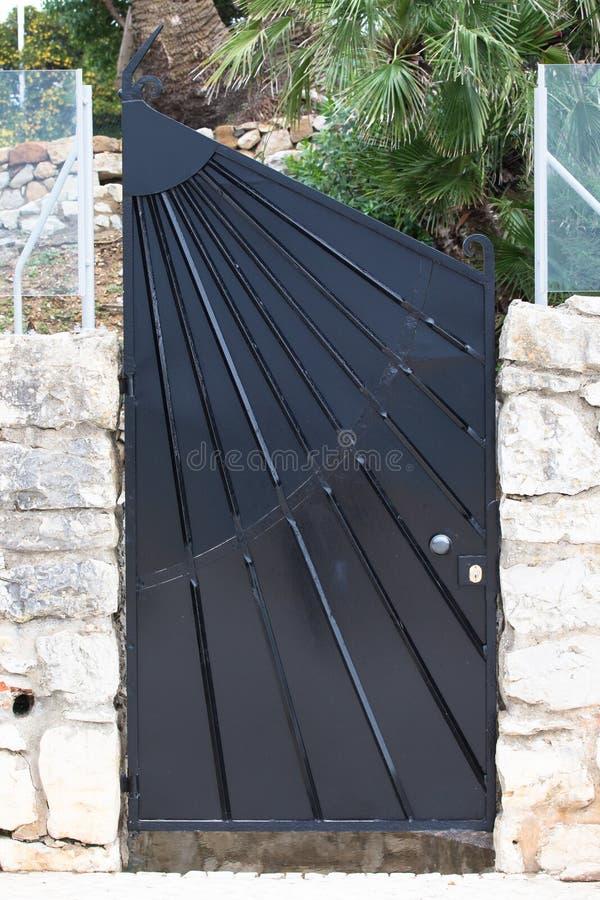 La porte moderne de fer dans le mur a été établie de la brique et du verre photo stock