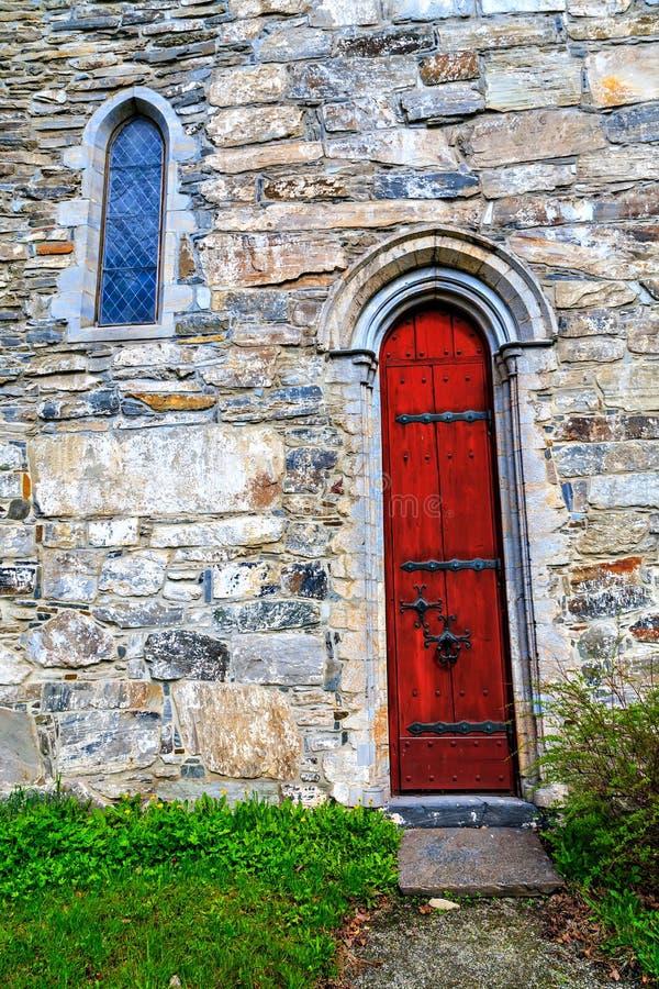 La porte rouge à l'église en pierre, Norvège photos libres de droits