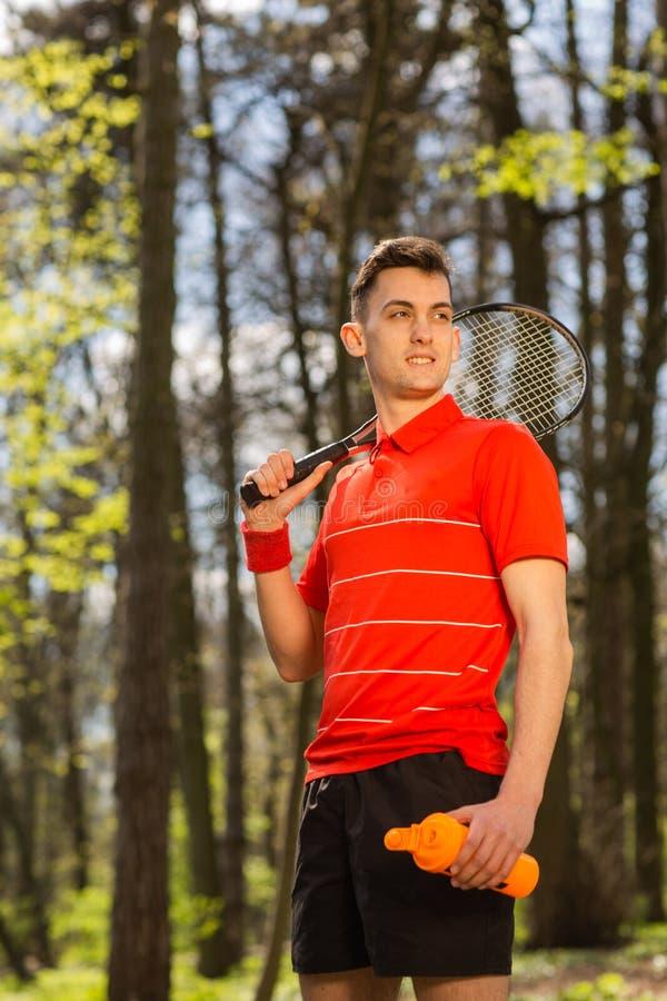 La posa dell'uomo con una racchetta di tennis e una termocoppia arancio, sui precedenti del parco verde Concetto di sport immagine stock