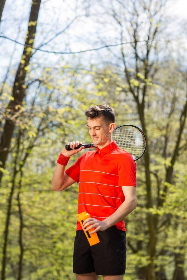 La posa dell'uomo con una racchetta di tennis e una termocoppia arancio, sui precedenti del parco verde Concetto di sport immagini stock