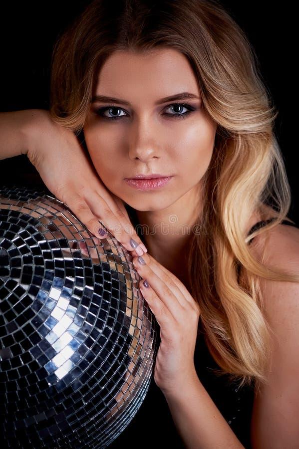 La pose blonde dans le style d'Abba tient une boule de disco L'ère de la disco Boîte de nuit, dansant photographie stock