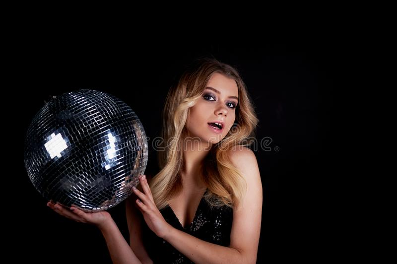La pose blonde dans le style d'Abba tient une boule de disco L'ère de la disco Boîte de nuit, dansant image libre de droits