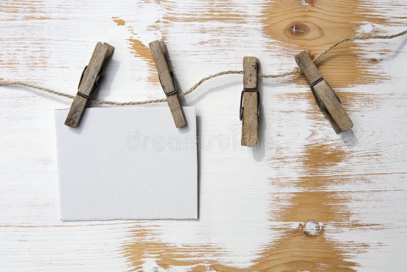 La pose de papier peint blanche sur une corde à linge sur le fond en bois rustique image libre de droits