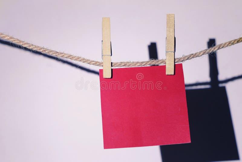 La pose de papier peint rouge de note sur la corde sur le mur blanc photos stock