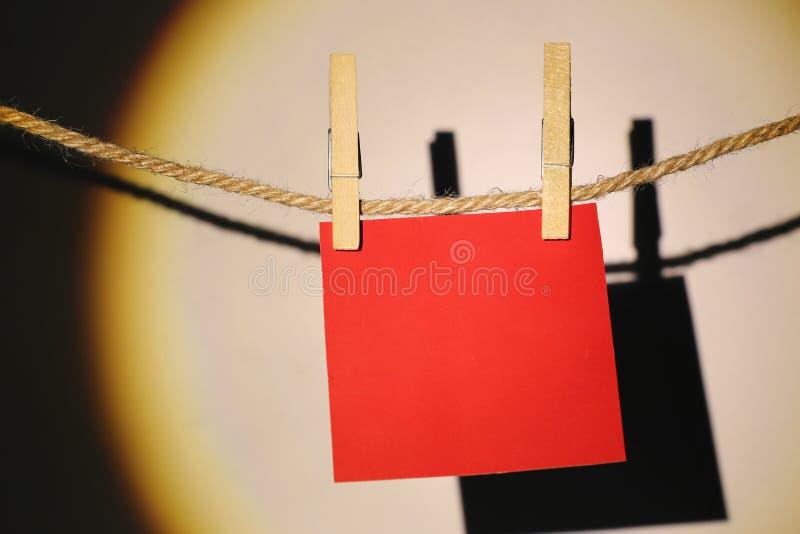 La pose de papier peint rouge de note sur la corde sur le mur blanc photos libres de droits