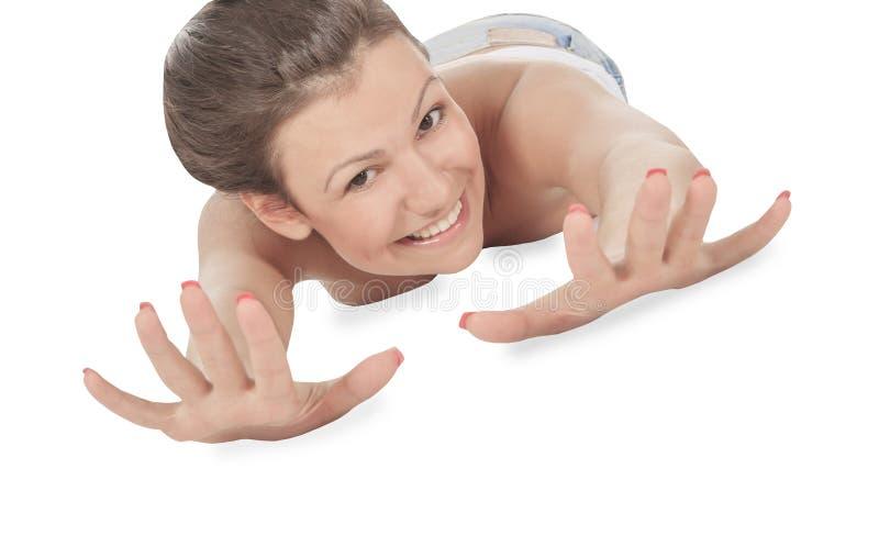 La pose femelle sur le plancher étirant le sien arme en avant image libre de droits