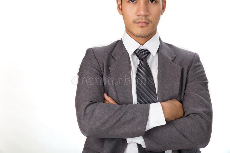 La pose réfléchie d'homme d'affaires à l'appareil-photo avec des bras a croisé sur le blanc image stock