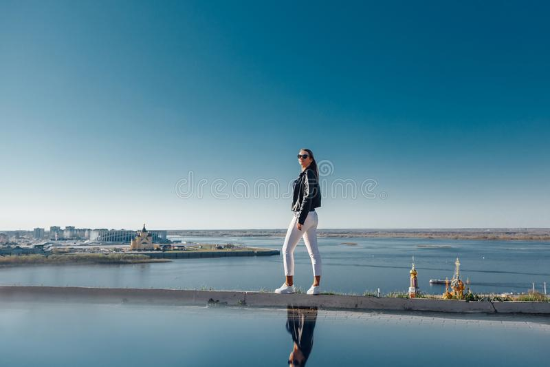 La position élégante de fille sur une montagne, ciel bleu s'est reflétée dans l'eau photos stock
