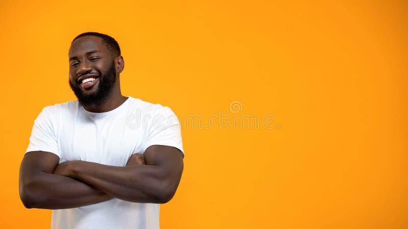 La position afro-am?ricaine belle d'homme avec des mains a crois?, regardant la cam?ra photo stock