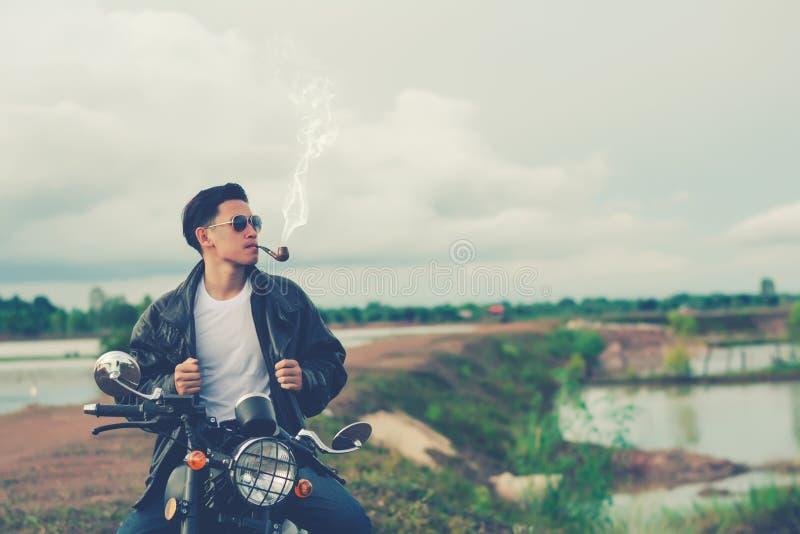 La position d'homme de cycliste fume avec sa motocyclette près du lac naturel et beau, appréciant la liberté et le mode de vie ac photo stock