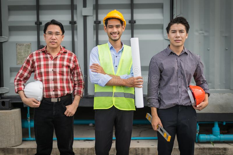 La position d'ingénieur, d'agent de maîtrise et d'employés au chantier de construction sont photographie stock