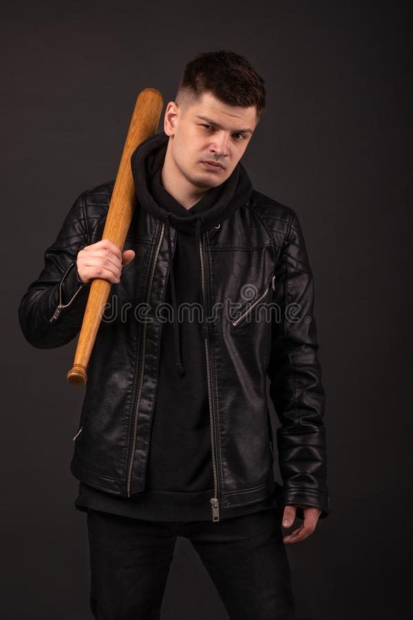 La position de port de veste en cuir de jeune homme dans la pose de combat avec la batte de baseball sur le fond fonc? dans le st photo libre de droits