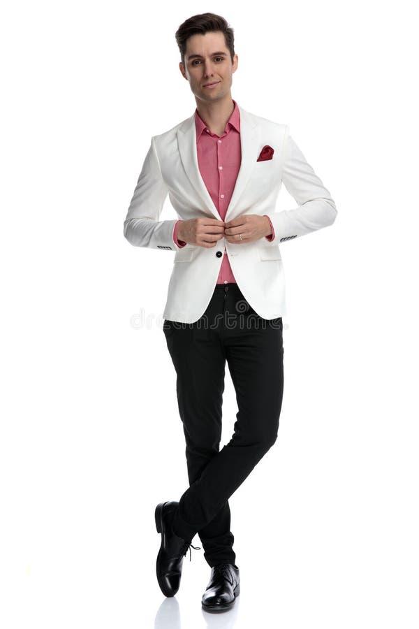 La position de sourire d'homme d'affaires avec des jambes croisées ferme sa veste image stock