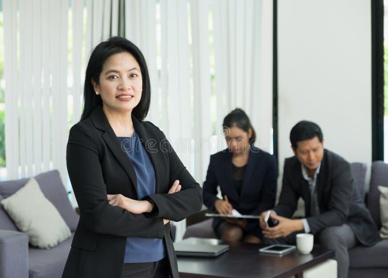 La position et la croix femelles de chef de femme d'affaires arment avec l'équipe dedans images libres de droits