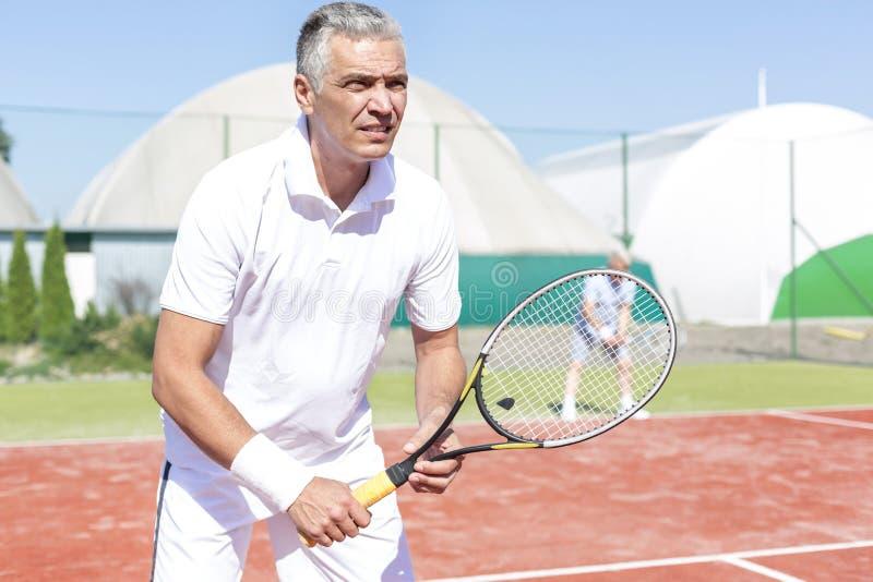 La position mûre sûre d'homme avec la raquette de tennis contre l'ami jouant des doubles s'assortissent sur la cour photo libre de droits