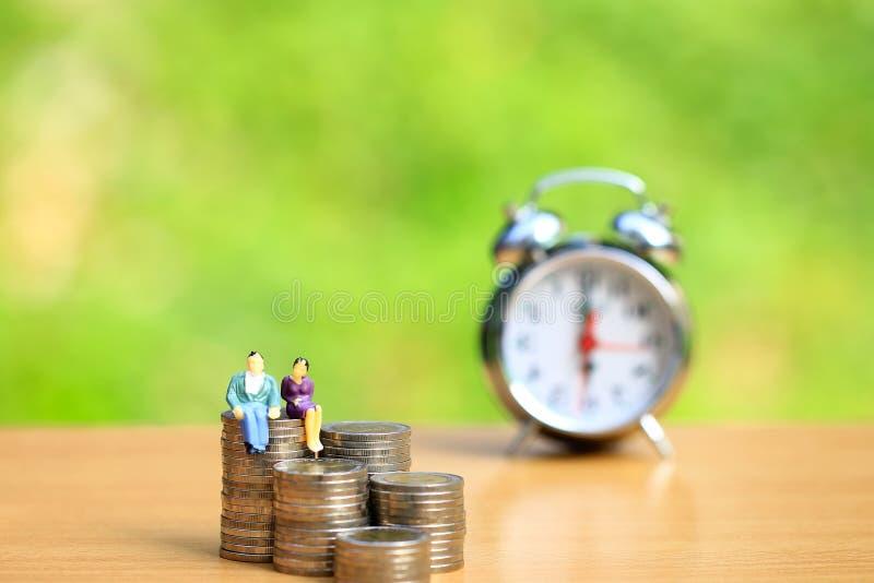 La position miniature de couples sur l'argent de pièces de monnaie avec l'horloge d'alrm sur le fond vert naturel, épargnent l'ar photographie stock
