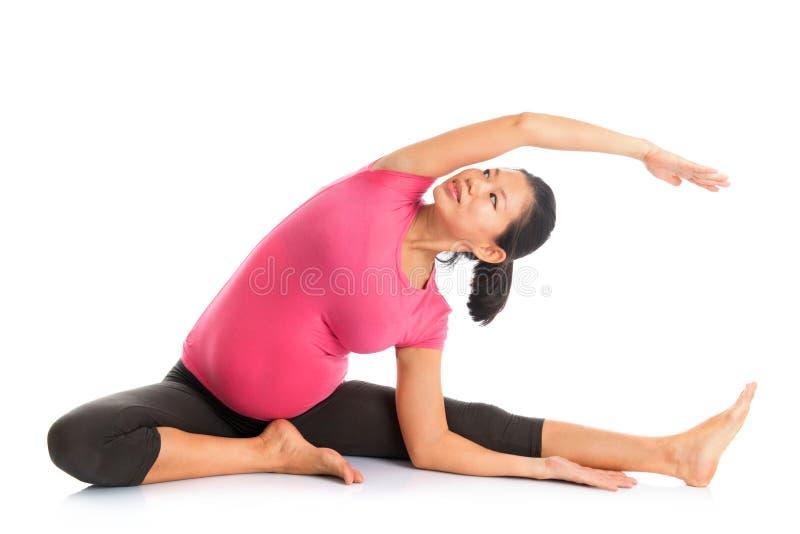 La posizione di yoga della donna incinta ha messo l'allungamento a sedere laterale. immagine stock