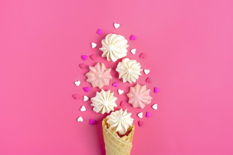 La postal de la tarjeta del día de San Valentín - merengue y caramelo en la forma de un cono de helado del corazón y en un fondo  imagen de archivo