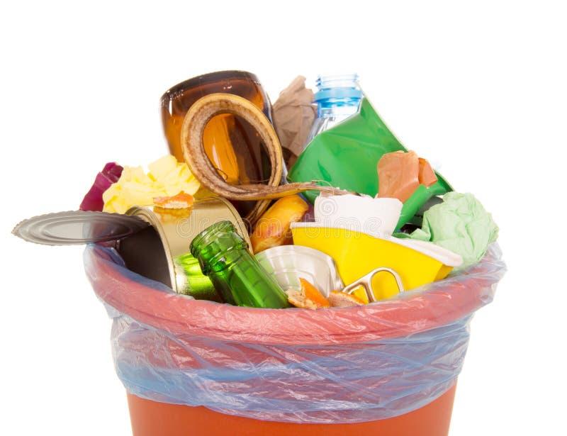 La poubelle a complètement rempli de déchets de ménage d'isolement sur le blanc image stock