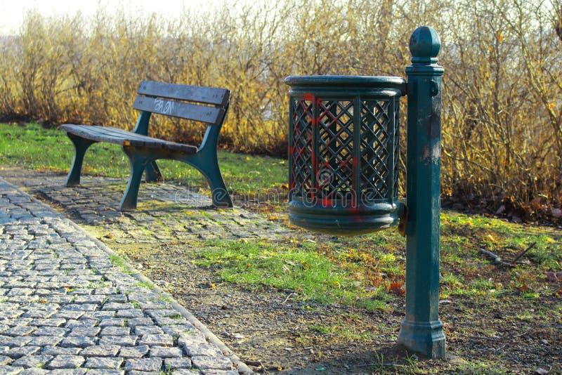 La poubelle verte de poubelle en métal tient sur l'herbe tout près un banc en métal avec les planches en bois en parc de ville image stock