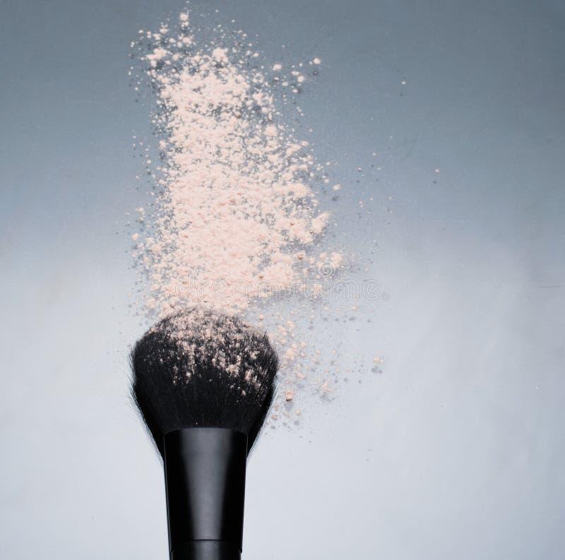 La poudre beige cosmétique sur la dispersion noire de brosse composent le bleu de texture de beauté photographie stock libre de droits