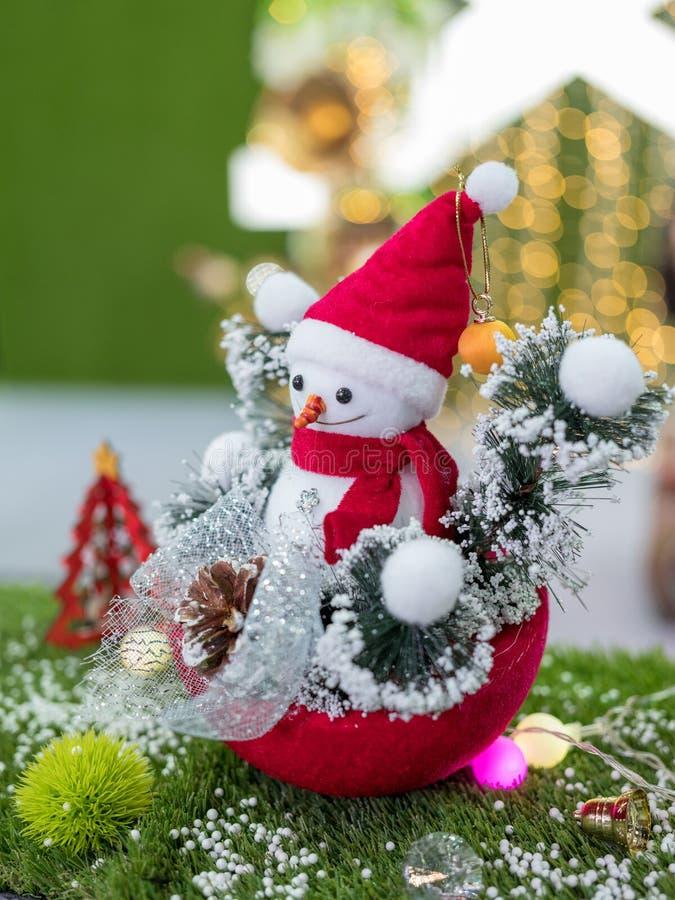La poupée de bonhomme de neige dans un chapeau rouge et l'écharpe décorent pour les salutations de la saison de Noël images stock