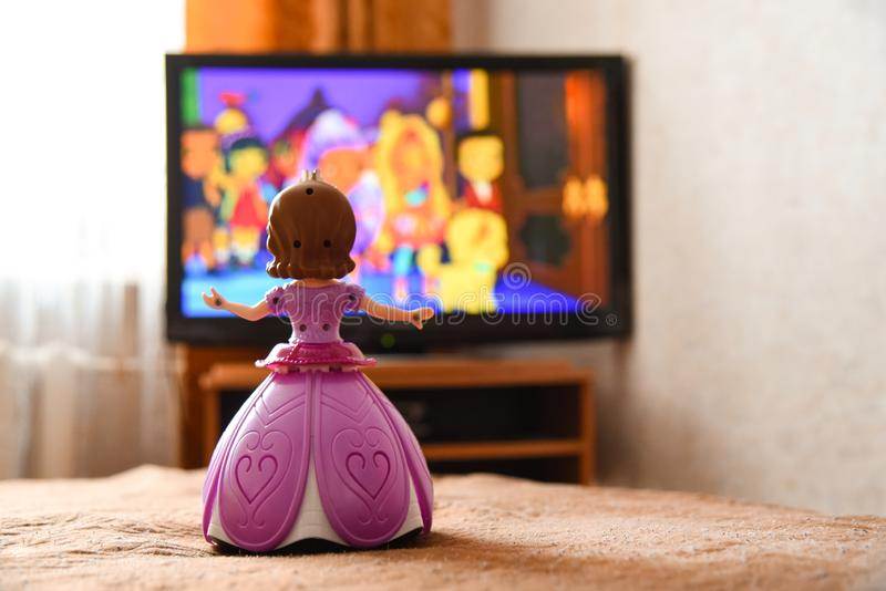 La poupée de jouet dans une robe rose observe une bande dessinée à la TV photographie stock