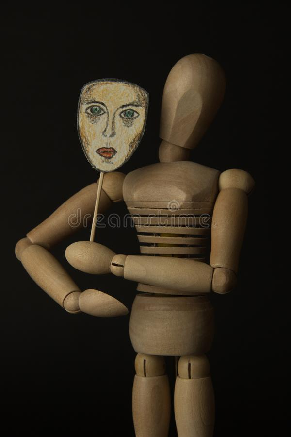 La poupée en bois sur des charnières tient un masque dans des mains et couvre son visage photos libres de droits