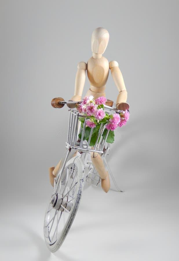 La poupée ou le mannequin en bois monte une vieille bicyclette blanche avec le panier images stock