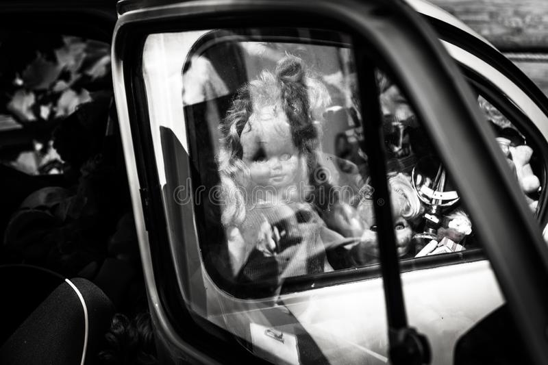 La poupée regarde hors de la fenêtre de voiture, fond pour Halloween, image effrayante image libre de droits