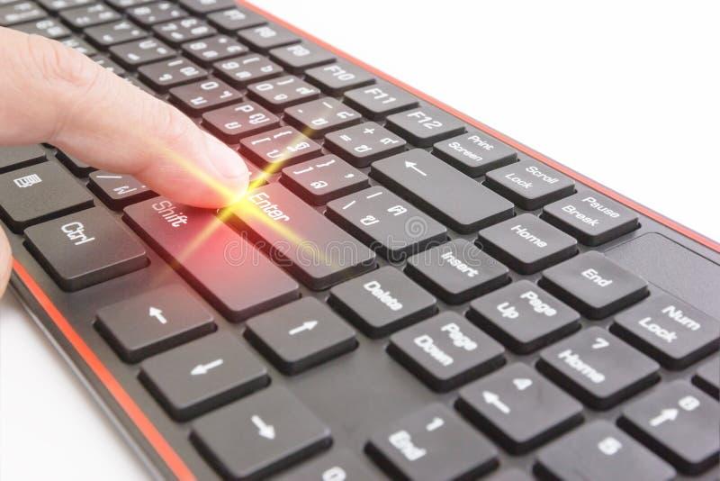 La poussée de doigt entrent dans le bouton sur le clavier noir, effet de la lumière photographie stock libre de droits