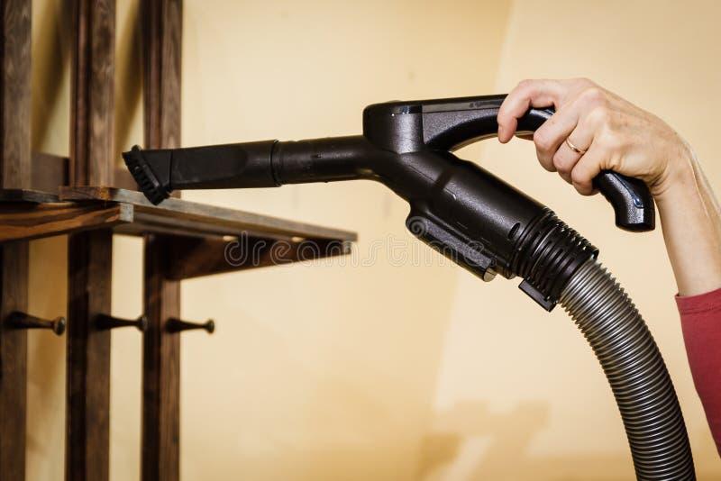 La poussière de nettoyage de femme sur le cintre photographie stock libre de droits