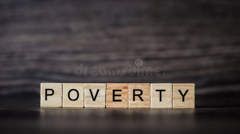La povertà di parola ha composto delle plance di legno leggere su un buio di legno fotografia stock