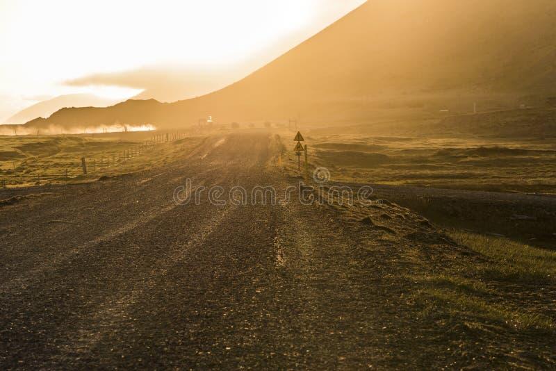 La précaution se connectent la route de gravier avec le coucher du soleil d'or dans Stokksnes, glace photo libre de droits