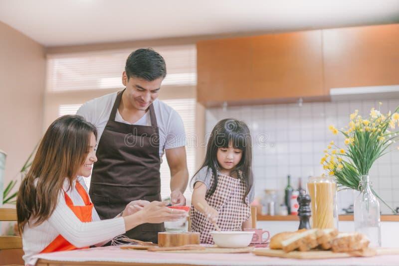 La préparation de parent d'aide de fille font le concept de la famille cuire au four images libres de droits