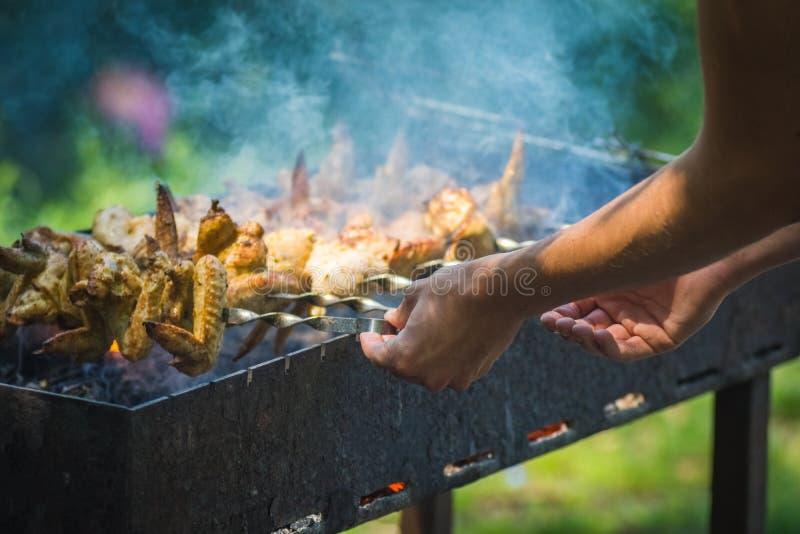 La préparation des brochettes de poulet sur un brasero sur des brochettes, du côté droit dans le cadre de la main, des brochettes image stock