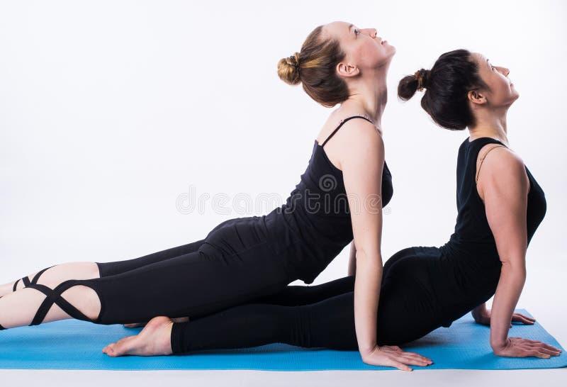 La pratica di forma fisica, un gruppo di due giovani di bella misura che risolvono in società polisportiva, facente l'allungament immagini stock libere da diritti