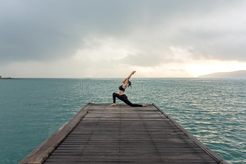 La pratica di yoga equilibrata stile di vita sano della donna medita ed energia su ponte nella mattina fotografia stock libera da diritti