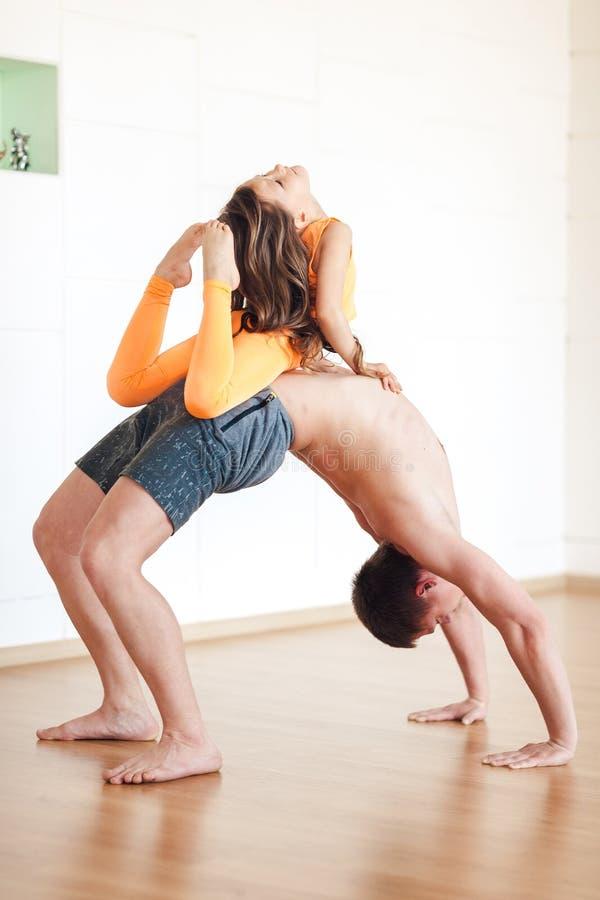 La pratica di yoga, un uomo sta stando sul ponte, una bambina è immagini stock