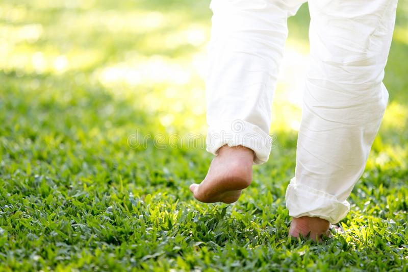 La pratique de la promenade dans les deux sens dans l'herbe des hommes dans le pantalon blanc, la méditation, paisible et régénér images libres de droits