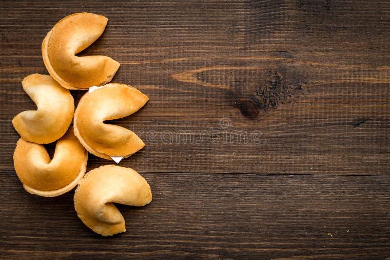 La predicción en galleta de la suerte en plano de madera del fondo pone la maqueta fotos de archivo