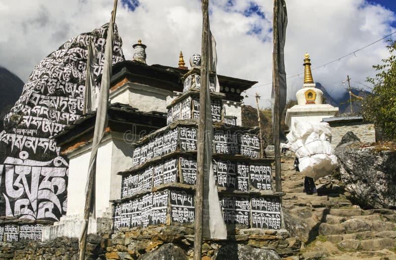 La preghiera di Stupa del monastero buddista inbandiera le montagne dell'Himalaya del villaggio del Nepal immagini stock libere da diritti