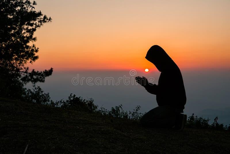 La preghiera manuale dell'uomo cristiano Siluetta immagini stock