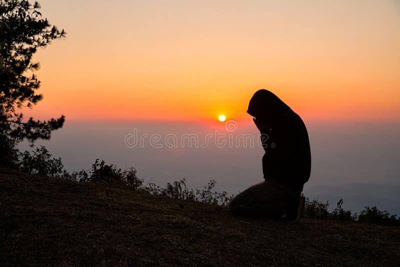 La preghiera manuale dell'uomo cristiano Siluetta immagine stock