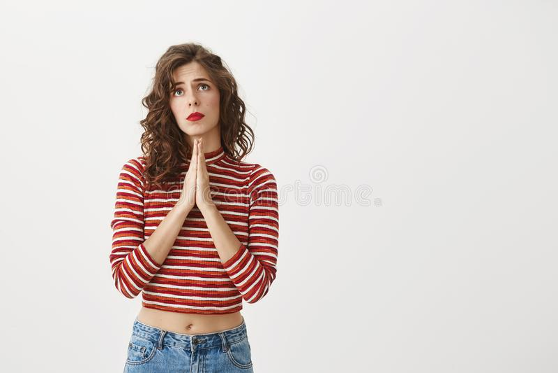La preghiera può fare i miracoli Il colpo dello studio di bello modello europeo che si tiene per mano dentro prega e che cerca co fotografie stock